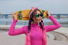 Brightly dressed girl with skateboard in the city royalty free stock photos