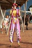 A brightly dressed stilt walker juggling royalty free stock image
