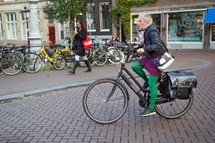 A brightly dressed woman on a bicycle. Amsterdam, Netherlands. A brightly dressed woman on a bicycle in the historical center of Amsterdam, the Netherlands Royalty Free Stock Photos