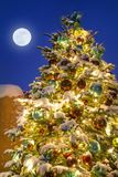 Brightly Glowing Christmas Tree in Santa Fe New Mexico. This wonderfully decorated Christmas Tree in Santa Fe New Mexico glows brightly at night as a light snow Stock Photography