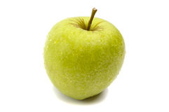 A brightly green apple in droplets of dew isolated Stock Photography