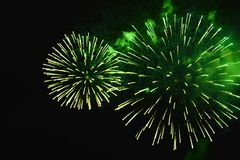 Brightly green color fireworks on dark background, shaped in the royalty free stock photography