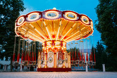 Brightly Illuminated Empty Carousel Merry-Go-Round. Nobody. The Brightly Illuminated  Empty Carousel Merry-Go-Round With Seats Suspended On Chains Without People Stock Photo