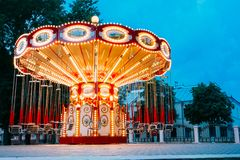 Brightly Illuminated Empty Carousel Merry-Go-Round. Nobody In Su. The Brightly Illuminated  Empty Carousel Merry-Go-Round With Seats Suspended On Chains Without Stock Photo