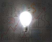 Brightly light bulb illuminated dark doodles wall Stock Photos
