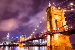 A brightly lit bridge at night in Cincinnati. On a cloudy night, a bridge in Cincinnati glows through the darkness Stock Photo