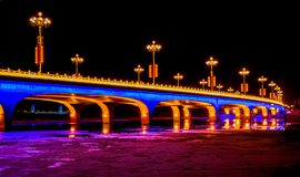 Brightly lit bridge at night royalty free stock photography