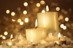 Brightly lit candles in wet snow royalty free stock photography