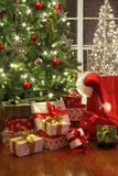 Brightly lit christmas tree with lots of gifts. Near window stock photo