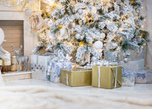 Brightly lit christmas tree with lots of gifts stock images