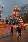 Brightly lit colourful fairground helter skelter. Balloon seller and a visiting couple. Winter Wonderland Hyde Park, London Royalty Free Stock Images