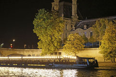 Brightly Lit Seine River Cruise Ship. Photo of brightly lit seine river cruise ship at night in paris france on 9/15/14 Stock Images
