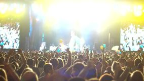 Brightly lit stage at a concert, the crowd, a large number of people at a rock concert, raised hands of musicians fans