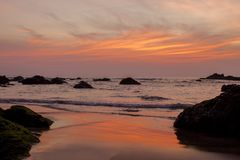 A Brightly orange blue gray purple cloud lines in the sunset sky over the sea with rocks and a sandy beach. Brightly orange blue gray purple cloud lines in the stock images