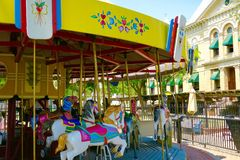 Brightly painted carousel in old town Hanford, California. Bright yellow, hot pink and gold adorn this attractive carousel near the old Kings County Courthouse Royalty Free Stock Photo