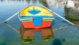 Brightly painted dinghy reflected in water Stock Images
