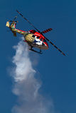 Brightly painted helicopter. Part of the Sarang air display team at the Aero India 2011 airshow, emitting smoke trails as it performs stunts stock images
