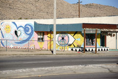 Brightly painted house facade in Yucca Valley. Yucca Valley, United States - December 24, 2015: The brightly painted facade of an old vintage shop in the desert stock illustration