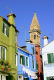Brightly painted houses. With a bell tower on the island of Burano near Venice Royalty Free Stock Image