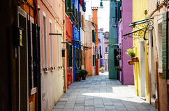 Brightly painted houses in alley, Burano, Venice Royalty Free Stock Images
