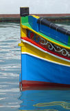 Brightly-painted Maltese Luzzu fishing boat. Close-up of part of traditional, brightly-painted Luzzu fishing boat in the bay at Marsaxlokk, Malta Stock Photos