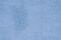 The brightly painted surface is covered with smoky dusty blue plaster. Background for copy space royalty free stock photos