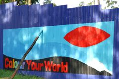 Brightly Painted Wall in Africa. Colorful metal wall almost finished being painted in Kampala, Uganda stock image