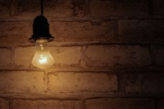 Brightly shining light bulb on a brick wall background. Energy saving concept. Background in a dark key, similar to the basement. Brightly shining light bulb on royalty free stock images