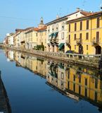 Brightly sunlit houses along the Naviglio Grande in Milan on a bright summer morning, reflected in the calm water of the canal royalty free stock image