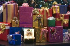 Brightly wrapped presents stacked under the Christmas tree stock photos