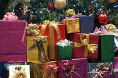 Brightly wrapped presents stacked under the Christmas tree stock images