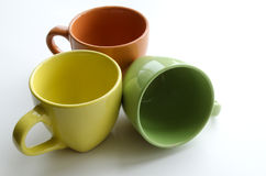 Brightly yellow, orange and green ceramic cups Royalty Free Stock Image