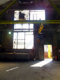 Brightness in a dirty window. Ray of sunlight entering through the open door of an industrial hall and brightness in a dirty window Royalty Free Stock Photos