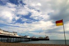 Brighton: bandiera e pilastro di salvataggio della spuma della spiaggia Fotografia Stock