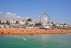 Brighton Beach ammucchiato con la ruota di Brighton fotografia stock