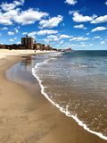 Brighton Beach in Brooklyn Blue Sky White Clouds. Nearly empty beach in early summer. New York City Brighton Beach in a Russian neighborhood. Clear blue water on Stock Photos