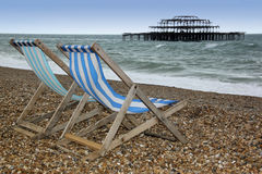 Brighton beach deckchairs west pier sussex england. Striped canvas deckchairs on brighton beach with the ruins of the west pier behind east suusex england Stock Images