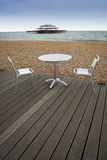 Brighton beach outside dining sussex england. Table and chairs on wooden decking of outdoor cafe on brighton beach seafront east sussex england Royalty Free Stock Images