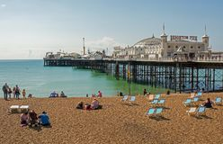 Brighton beach and pier, Sussex, England. People enjoying the seaside on beach by the pier at Brighton, East Sussex, England Royalty Free Stock Photo