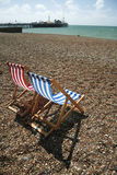 Brighton beach striped deck chairs. Pebble beach with striped canvas deckchairs, brighton, england Stock Image