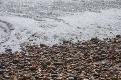 Brighton beach - waves and pebbles on a sunny day. This image shows a beach in Brighton on a sunny day. We can see some waves and wet pebbles stock image