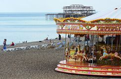 Brighton beach and West Pier. England. People enjoying the shingle beach with funfair roundabout and ruined West Pier in background. Brighton. East Sussex Royalty Free Stock Image
