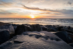 Brighton boulders sunrise. Looking over some large boulders at the sunrise in Brighton stock photography