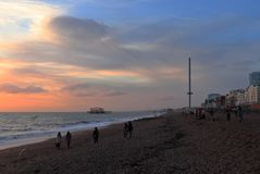 BRIGHTON, EAST SUSSEX, ENGLAND, UK - NOVEMBER 13, 2018: People enjoying the colors of sunset at Brighton Beach. royalty free stock photo