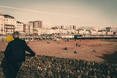 Brighton, England - October 19: Beautiful view of Brighton Pier with Brighton beach sea, sand and backside man of local people. Brighton, England - October 19 stock image