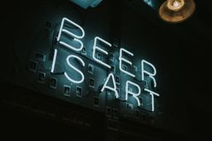 Brewdog pub indoors decoration in Brighton, United Kingdom. BRIGHTON, ENGLAND - October 26th, 2018: A `Beer is Art ` neon lettering lights in a wall at night stock photos