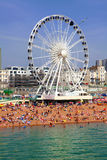 BRIGHTON -JULY 14,2013 - View the golden sand of Brighton beachfront to the ferris wheel and amusement park with groups of people. On the beach on July 14, 2013 stock photo
