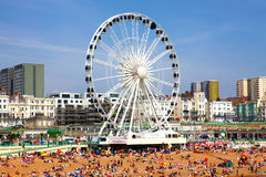 BRIGHTON -JULY 14 - View the golden sand of Brighton beachfront to the ferris wheel and amusement park with groups of people on th Stock Photography