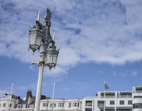 Brighton - the lamp post. This image shows a beach in Brighton, England with some people walking and chilling Royalty Free Stock Photography
