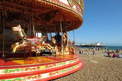 Brighton merry-go-round and Brighton Pier Palace Pier. Brighton, United Kingdom - July 5, 2015: Brighton, with its pebbly beach and fair rides, is one of the Stock Photography